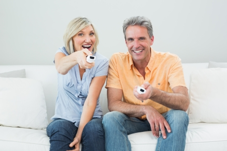 remote controls: Portrait of a relaxed cheerful couple with remote controls sitting on sofa in a house