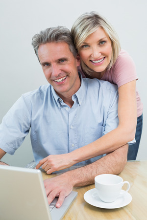 Portrait of a content casual couple using laptop at home photo