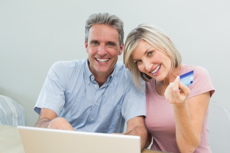 debit card: Cheerful couple doing online shopping with debit card and laptop in the living room at home