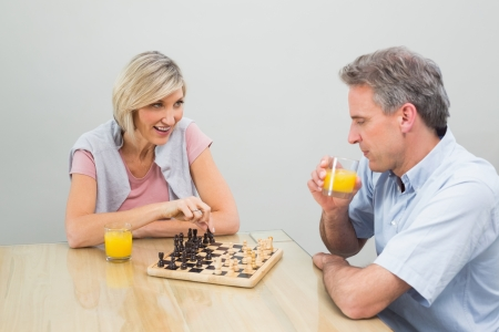 Concentrated woman and man playing chess at home photo