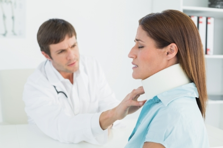 Side view of a male doctor examining a patients neck in medical office photo