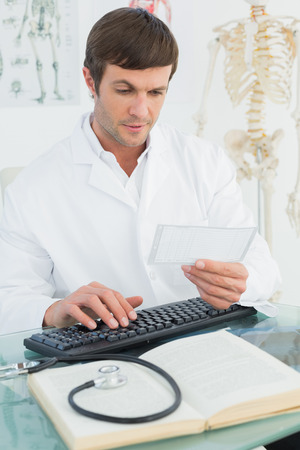 Concentrated male doctor reading a note at desk in medical office photo