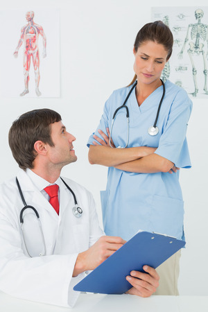 Male doctor with reports looking at nurse in the medical office photo