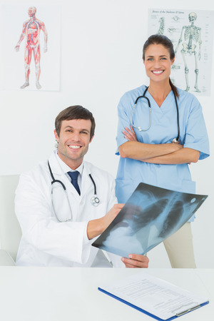 Portrait of a male doctor and female surgeon examining x-ray in a medical office photo