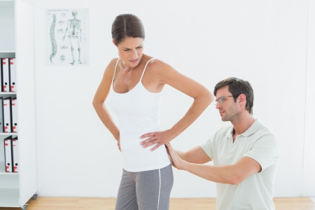 Side view of a male physiotherapist examining woman's back in the medical office photo