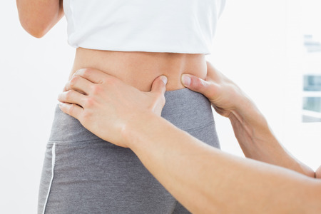 Close-up mid section of a physiotherapist examining womans back in the medical office Stock Photo