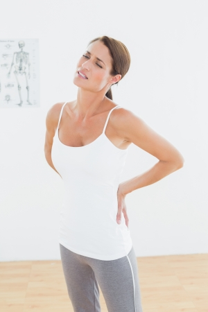 back muscles: Beautiful young woman with back pain standing in the medical office