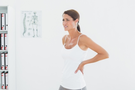 lower back: Side view of a beautiful young woman with back pain standing in the medical office