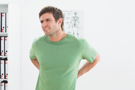Portrait of a handsome young man with back pain standing in the medical office photo