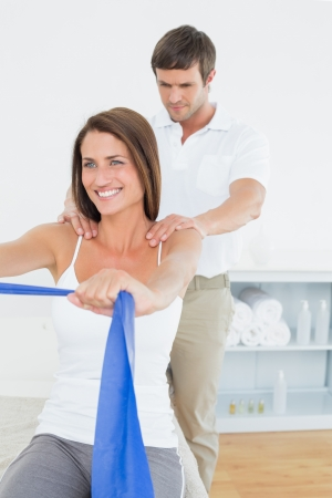 Male therapist assisting young woman with exercises in the medical office photo