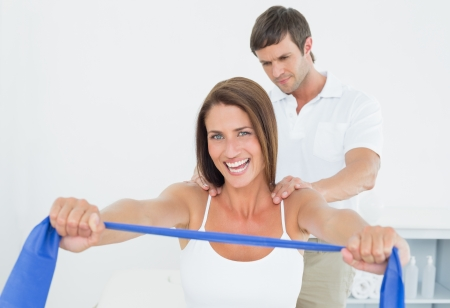 yoga to cure health: Male therapist assisting young woman with exercises in the medical office