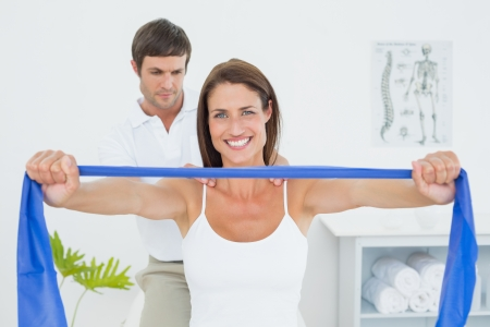 fisico: Terapeuta Hombre ayudar a la mujer joven con ejercicios en el consultorio m�dico Foto de archivo