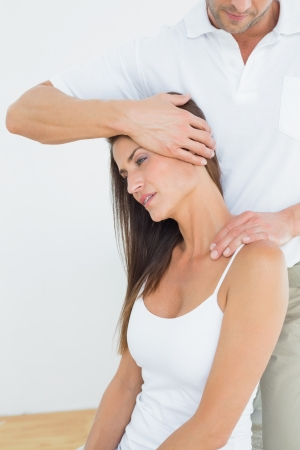 alternative therapies: Male chiropractor doing neck adjustment in the medical office