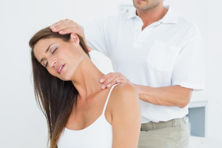 Male chiropractor doing neck adjustment in the medical office photo