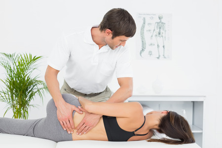 Male physiotherapist massaging womans back in the medical office Stock Photo