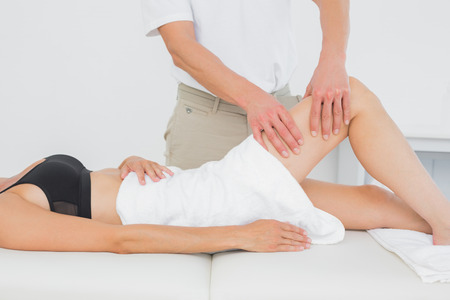 Male physiotherapist examining a young womans leg in the medical office photo
