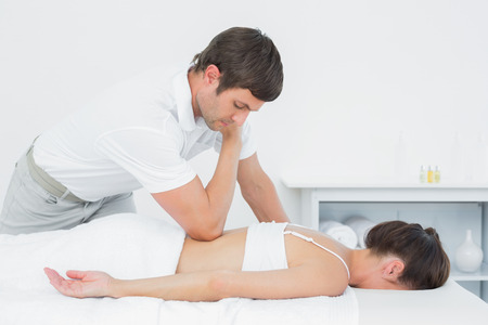 Male physiotherapist massaging woman's back in the medical office photo