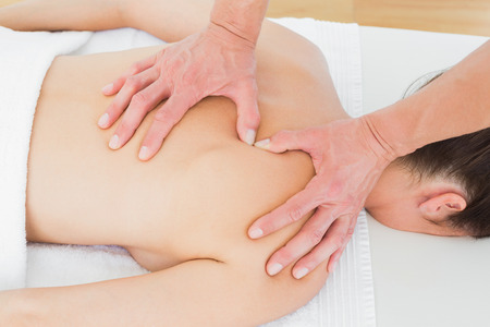 Close-up of male physiotherapist massaging womans back in the medical office photo