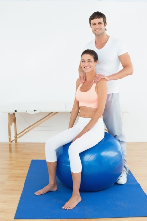 Young woman sitting on yoga ball while working with a physical therapist photo