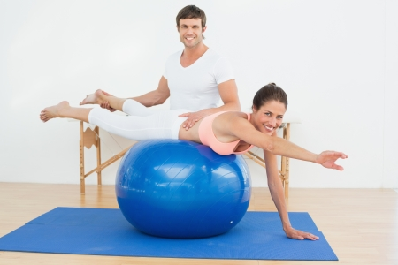yoga to cure health: Physical therapist assisting young woman with yoga ball in the gym at hospital Stock Photo