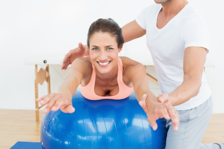 Physical therapist assisting young woman with yoga ball in the gym at hospital photo