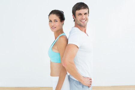 Portrait of a fit young couple standing in fitness studio Stock Photo