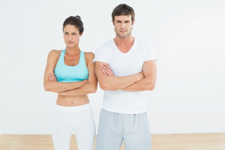 Portrait of a fit young couple with arms crossed standing in fitness studio photo