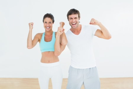 clenching fists: Portrait of a cheerful fit young couple clenching fists in the fitness studio