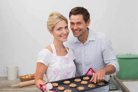 Portrait of happy young couple preparing cookies together in the kitchen at home photo