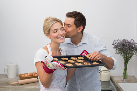 kiss biscuits: Man kissing womans cheek as she holds freshly baked cookies in the kitchen at home