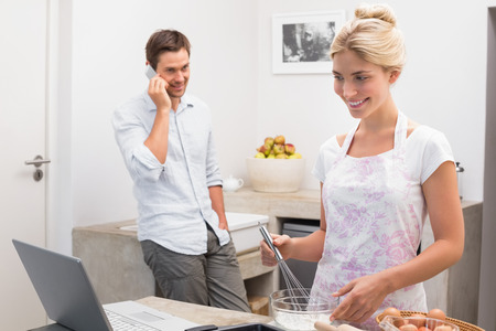 Smiling young woman preparing cookies while man on call in the kitchen at home photo