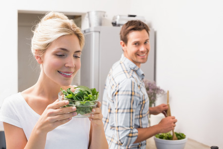Smiling young woman holding bowl of leaves with man preparing salad in the background in kitchen at home photo