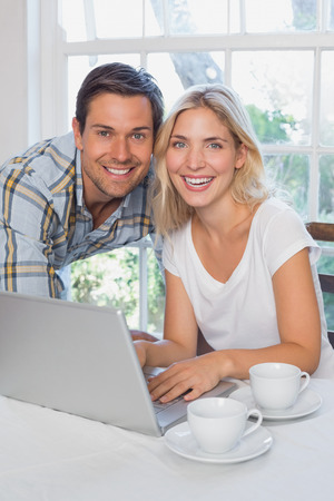 Portrait of a happy loving young couple with laptop at home photo
