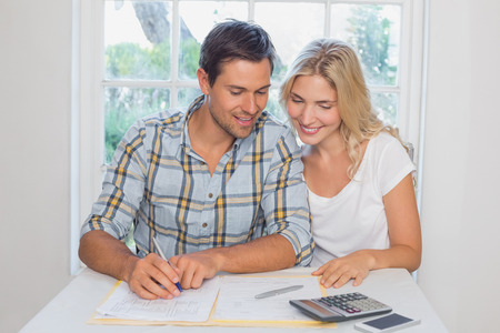 Happy young couple with financial documents and calculator sitting at home photo