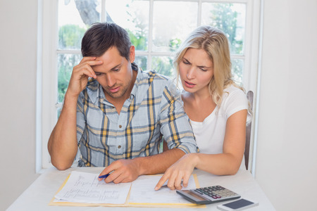 figuring: Worried young couple with financial documents and calculator sitting at home