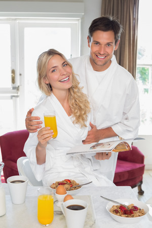 Portrait of a happy young couple having breakfast at home photo