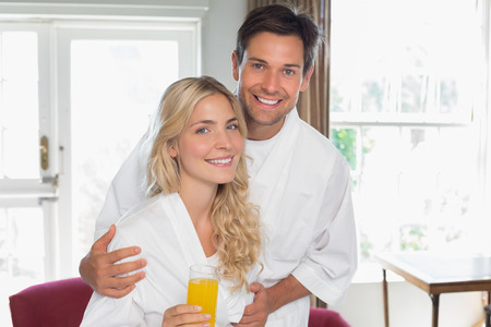 Portrait of a happy young couple with orange glass at home photo