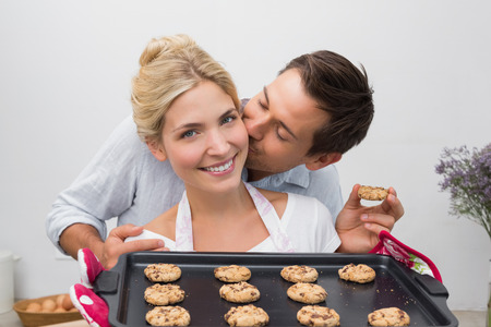 Man kissing womans cheek as she holds freshly baked cookies in the kitchen at home photo