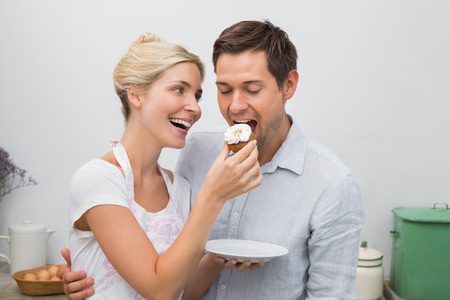 Happy young woman feeding man pastry in the kitchen at home photo