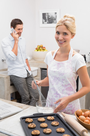 Portrait of a young woman preparing cookies while man on call in the kitchen at home