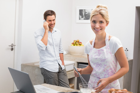 Portrait of a young woman preparing cookies while man on call in the kitchen at home photo