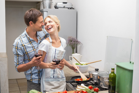 woman drinking wine: Portrait of a loving young couple with wine glass in the kitchen at home