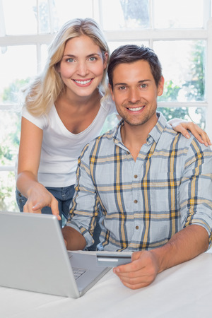 Smiling young couple doing online shopping through laptop and credit card at home photo