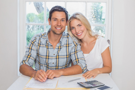 Portrait of a young couple with financial documents and calculator sitting at home