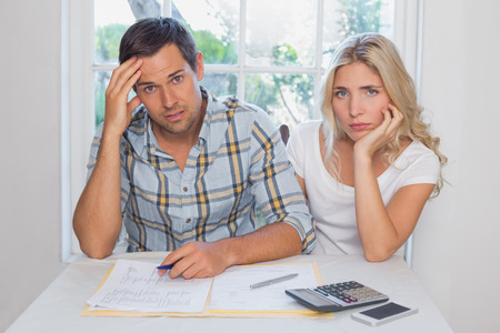 Worried young couple with financial documents and calculator sitting at home photo