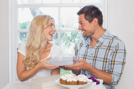 Beautiful young blonde receiving a gift box at home photo