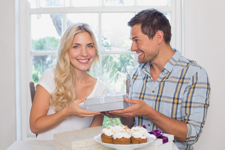 Portrait of a beautiful young blonde receiving a gift box at home photo