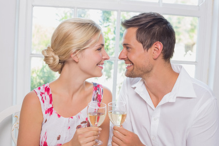 Happy loving young couple with wine glasses looking at each other at home