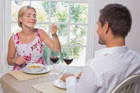Happy young couple enjoying food at home photo