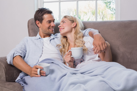 Relaxed loving young couple with coffee cups looking at each other in living room at home photo